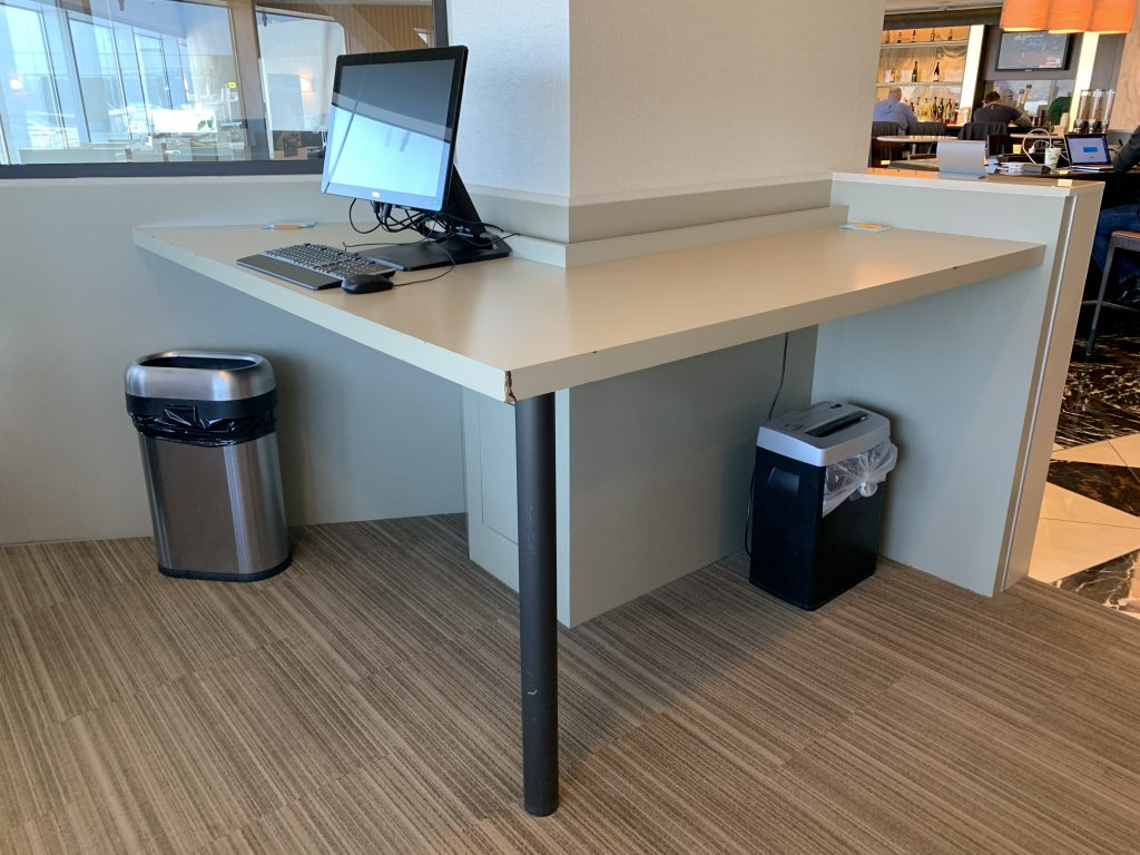 Computer station and standing desk at the American Airlines Admirals Club lounge.
