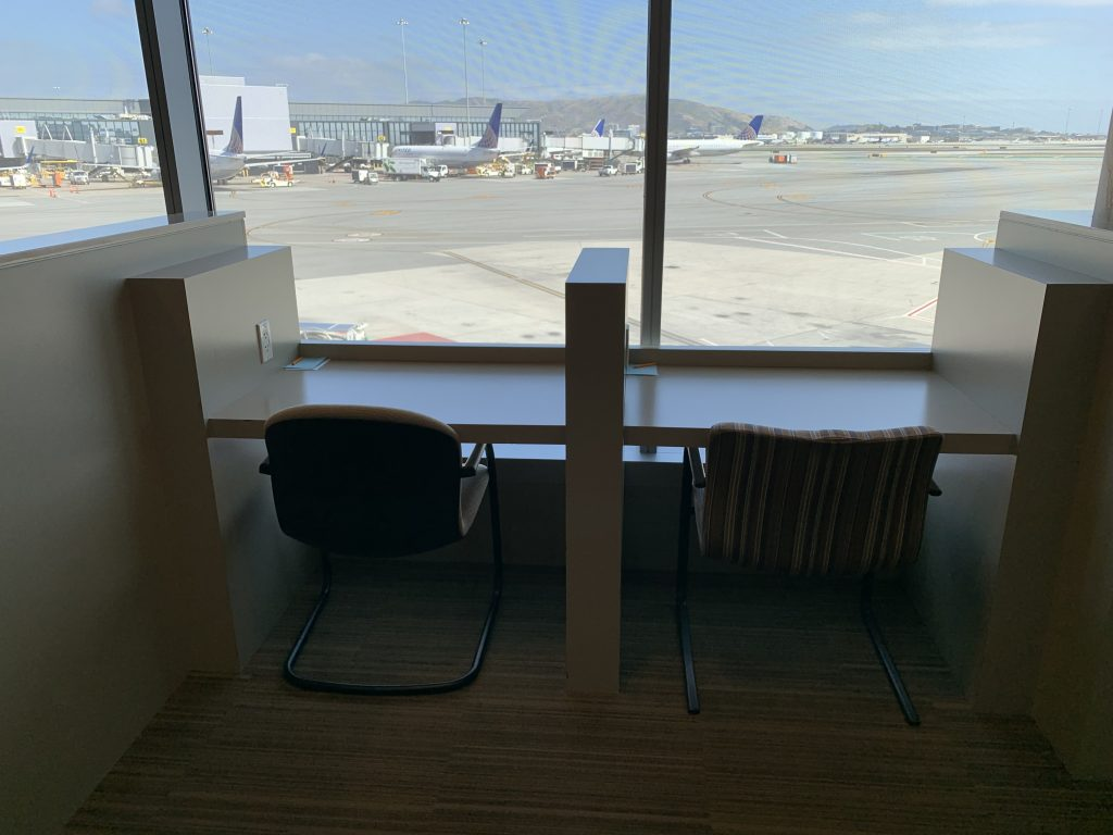 Seating at the Admirals Club SFO with runway view.