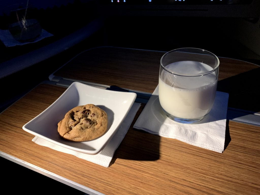 Warm chocolate chip cookie and glass of cold milk served aboard AA 16.