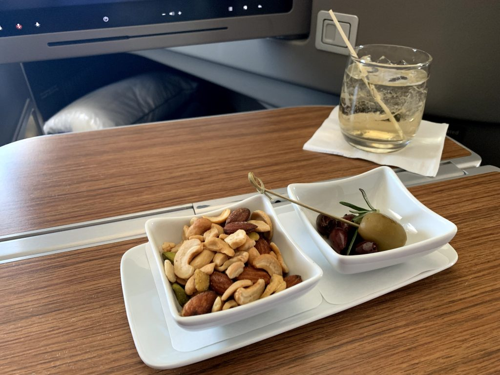 Warm nuts and a cocktail served onboard AA First Class.