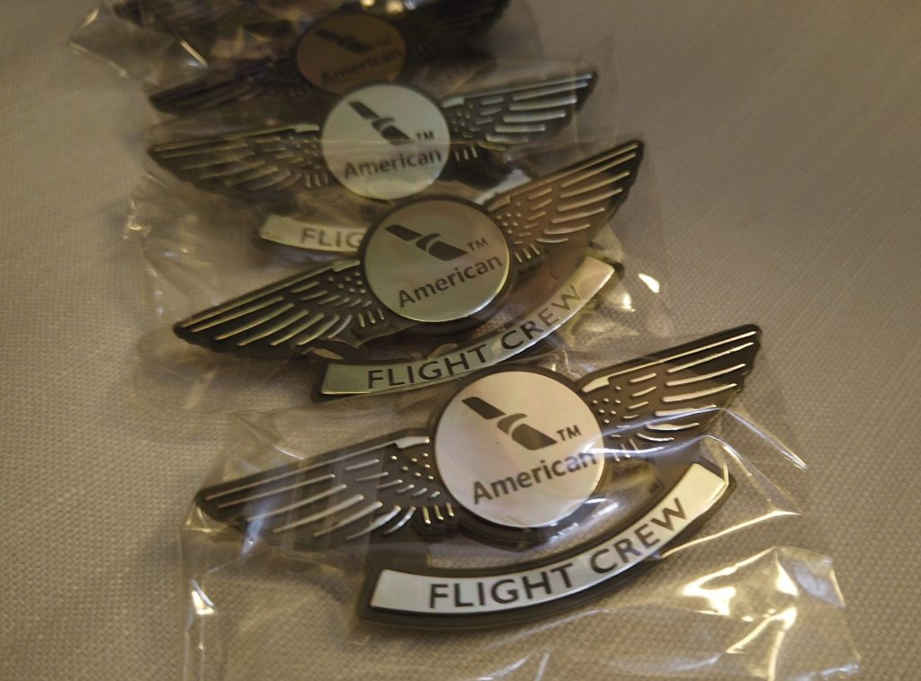 "Gold-tone ""Flight Crew"" pins provided to passengers in First Class on American Airlines."